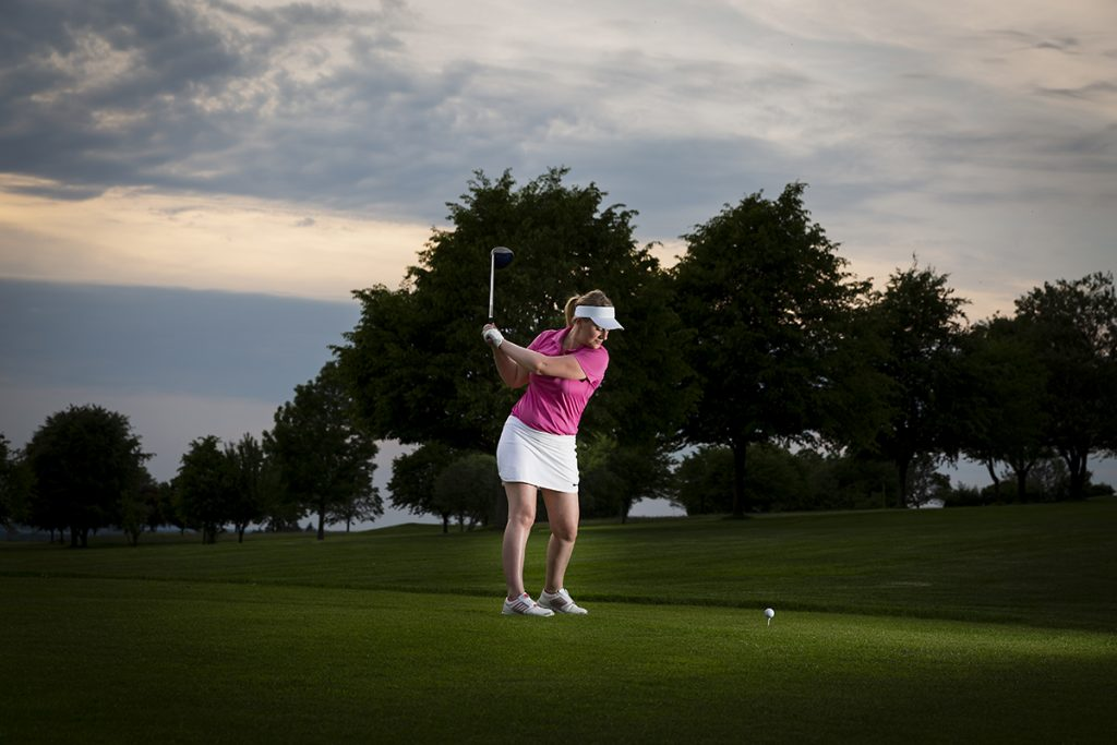 Golferin beim Abschlag bei Abendstimmung