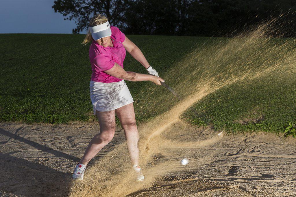 Golferin im Bunker, fliegender Sand
